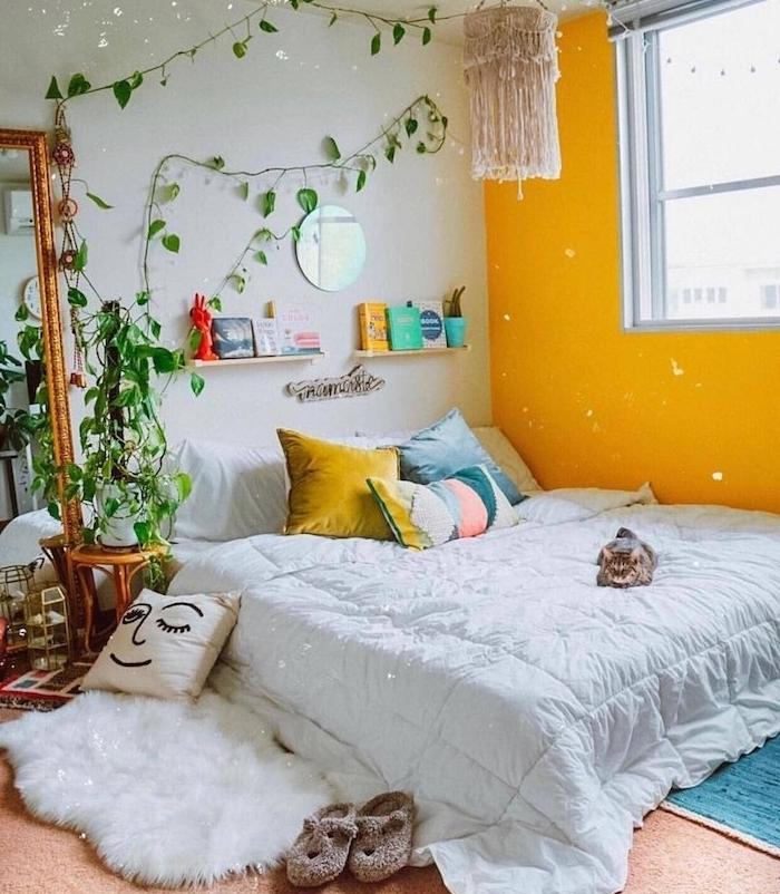 ambiance cosy dans chambre boheme chic, mur d accent peinture jaune, lit bas décoré de coussins colorés, plante verte grimpante d interieur, tapis peau de mouton, miroir rectangulaire vintage