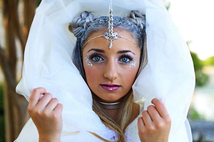 look licorne maquillage irisé en tons du violet avec paillettes dessous les yeux, coiffure de festival avec double buns tressés