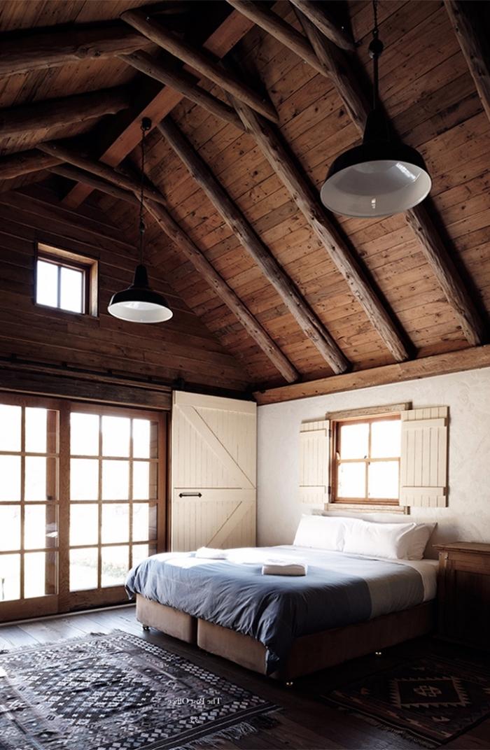 exemple de grange aménagée de style chalet, décoration chambre blanche et bois foncé au plafond haut avec sol bois foncé