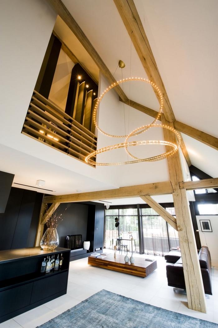 idée aménagement grange de style moderne, décoration studio loft aux murs blancs avec pan de mur en noir mat