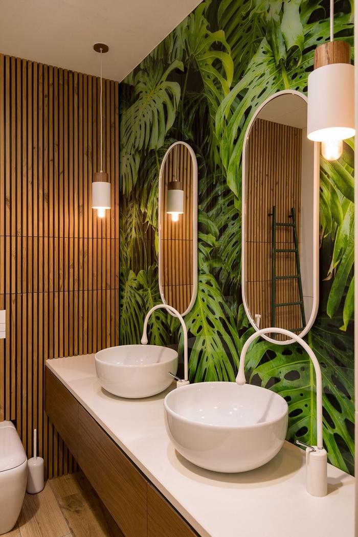 toilette deco tropicale avec papier peint trompe l'oeil à motifs feuilles monstera et lambris bois, meuble lavabo toilette bois et blanc