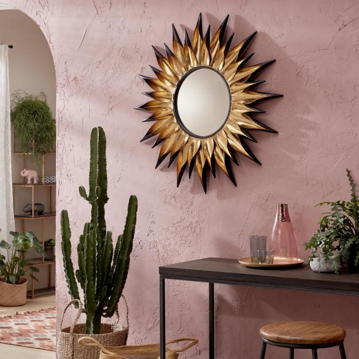 modèle de miroir soleil doré avec rayons à pointes noires, décoration salon exotique aux murs rose pastel avec plantes vertes