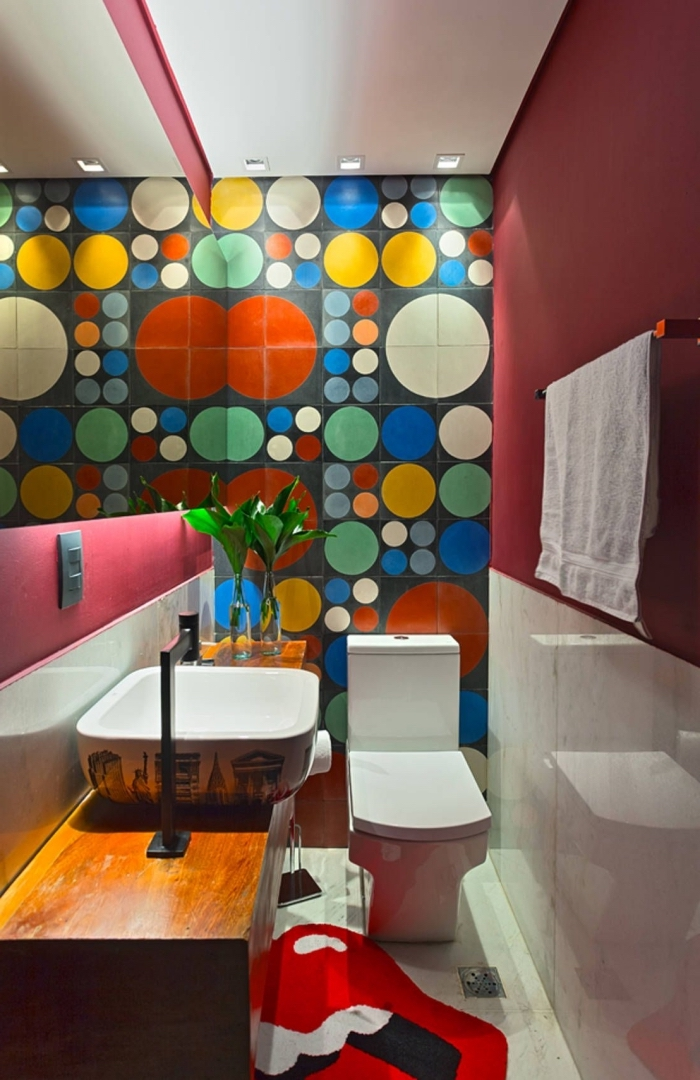 deco toilettes originales, modèle toilettes aux murs rouges avec faïence multicolore aux motifs géométriques