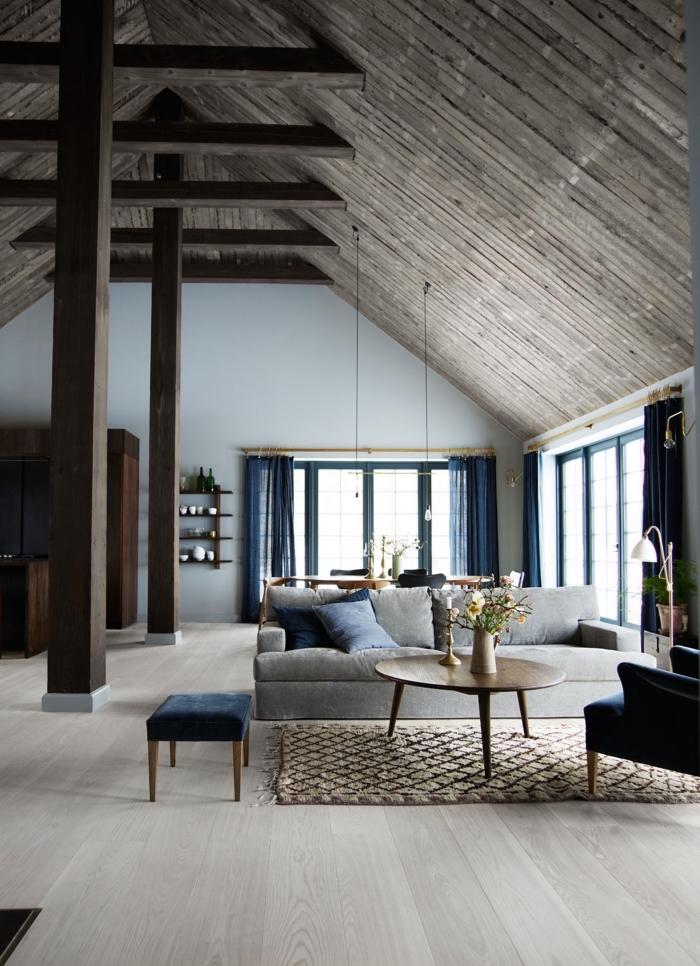 projet transformation grange en habitation, décoration salon loft aux murs blancs avec plafond bois foncé et meubles gris et bleu marine