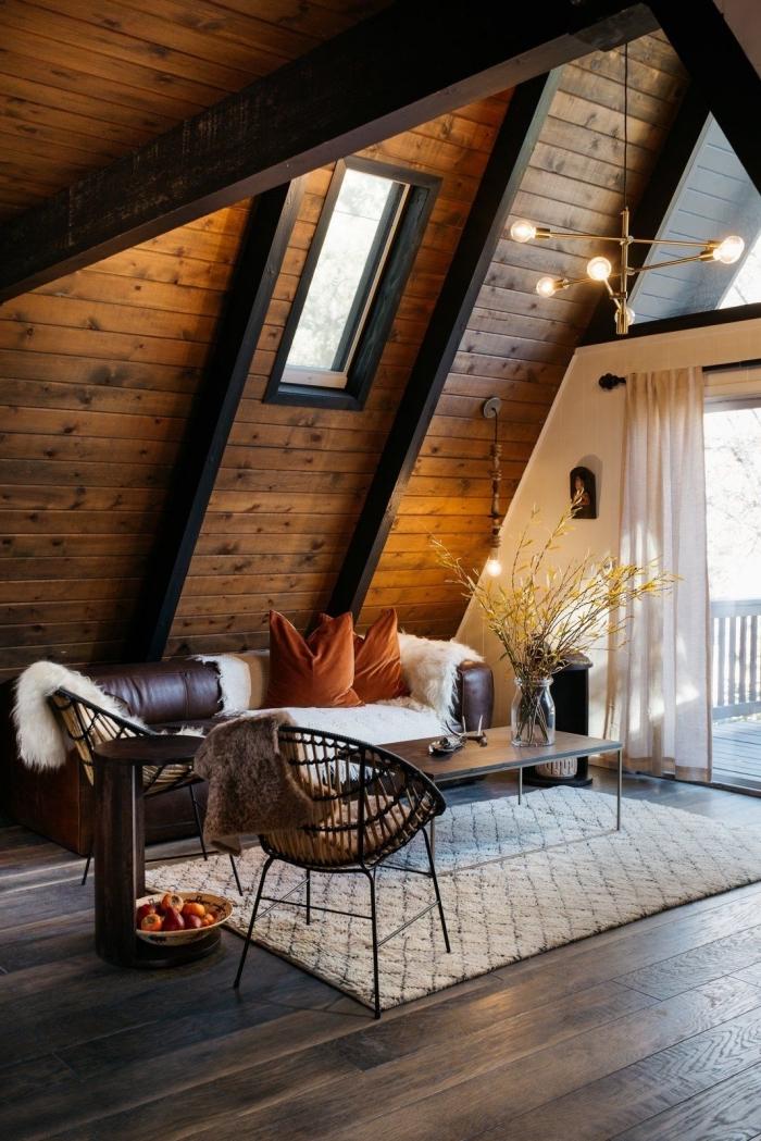 exemple de grange aménagée moderne, décoration style chalet en bois foncé avec meubles canapé cuir et table métal