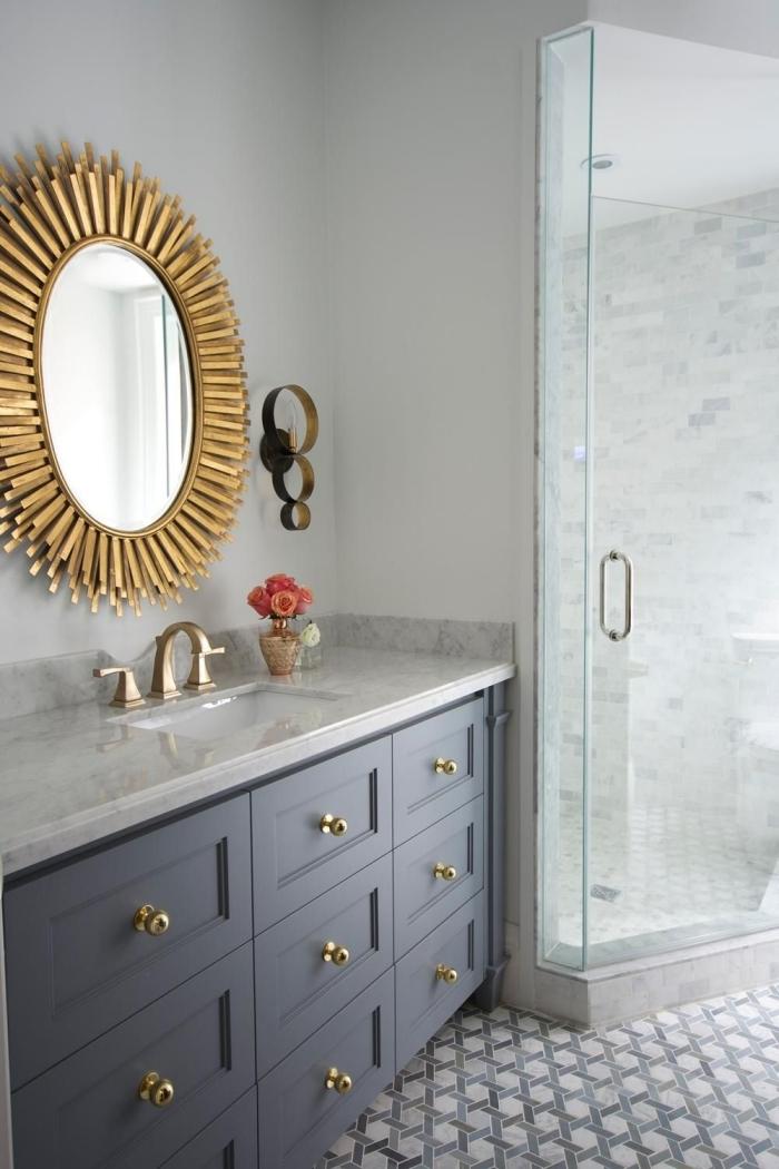 modèle de miroir en bois dans une salle de bain aux murs blancs avec carrelage sol motifs hexagonaux et finitions dorées
