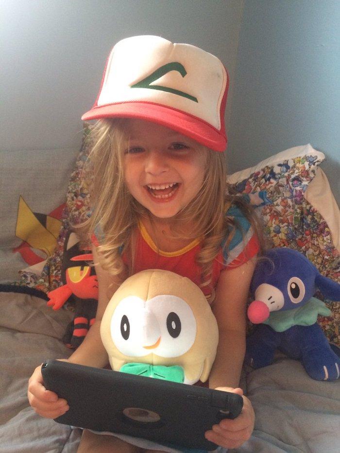 Pokemon deguisement bebe halloween, les costumes pour les plus petits, fille adorable qui joue à un jeu vidéo en costume de Ash de Pokemon