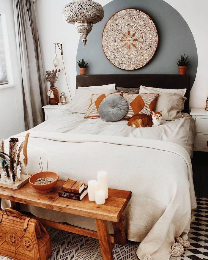 deco berbere dans une chambre a coucher adulte, linge de lit blanc, coussins orientaux, bout de lit banc en bois, tapis noir et blanc, lampe suspension orientale, peinture murale geometrique
