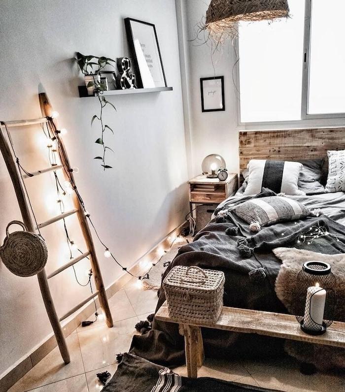echelle bois deco avec guirlande lumineuse, linge d elit gris et blanc, bout de lit en banc de bois brut, suspension originale, style deco berbere