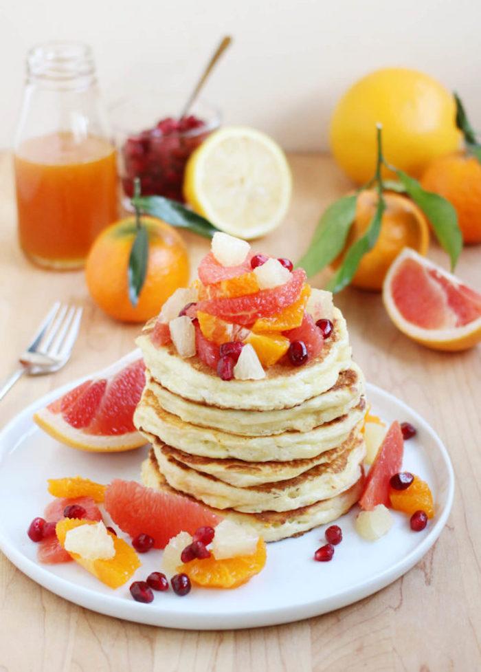 crepes simples aux fruit tropicaux, pamplemousse, орorange et grenade en top dans une assiette blanche