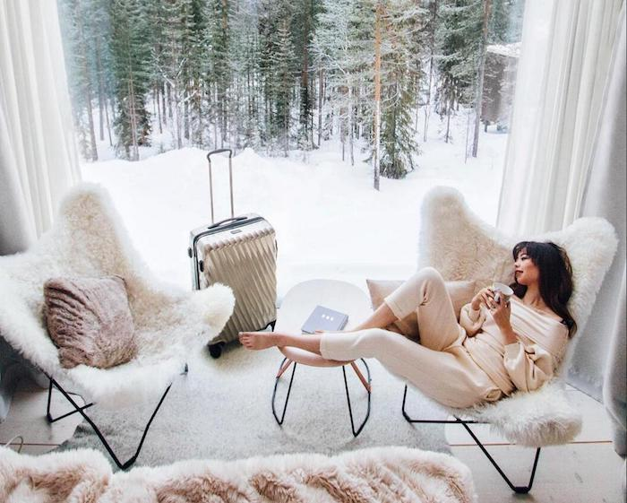 chambre avec verriere exterieure, fauteuil cosy, image cocooning femme qui se repose sur un fauteul scandinave, tapis cocooning, vue sur montagne en neige
