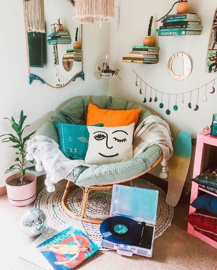 coin lecture cosy en fauteuil cocooning décoré de coussins colorés, tapis rond tressé, étagères murales flottantes avec piles de livres