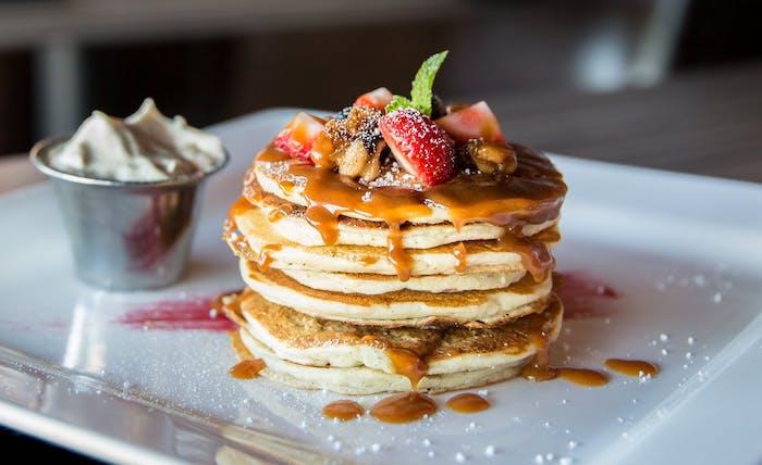 recette de pancake américain servi avec du caramel fait maison, fruits rouges et sucre glace
