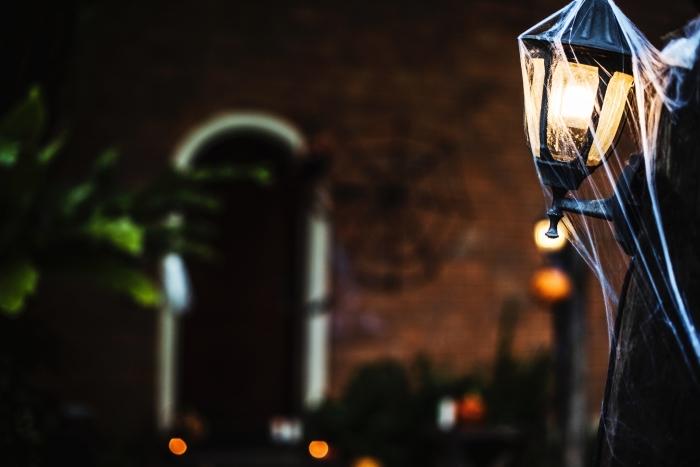 fond d'écran horreur, photo paysage urbain devant une maison à façade décorée pour halloween avec toile d'araignée et lanternes