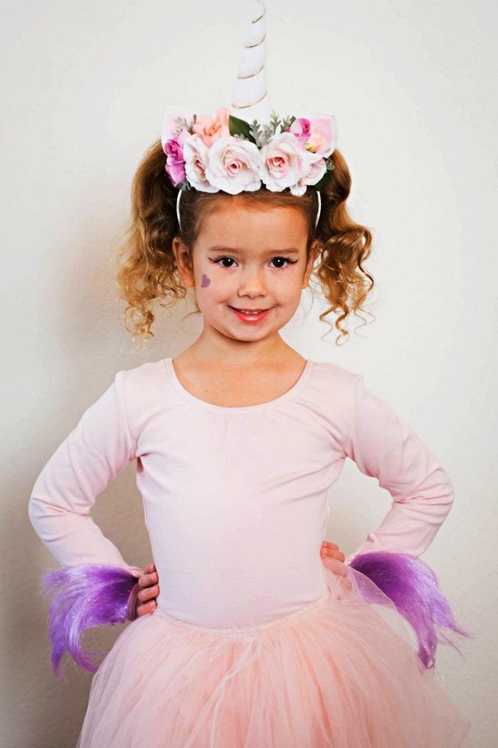 déguisement licorne fille avec jupe tutu rose et un serre-tête licorne avec fausses fleurs, maquillage de licorne fille avec petit dessin coeur violet sur la joue