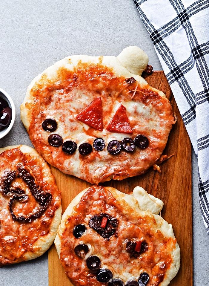 pizza halloween en forme de citrouille effrayante, mini-pizza d'halloween au fromage, tomates et olives