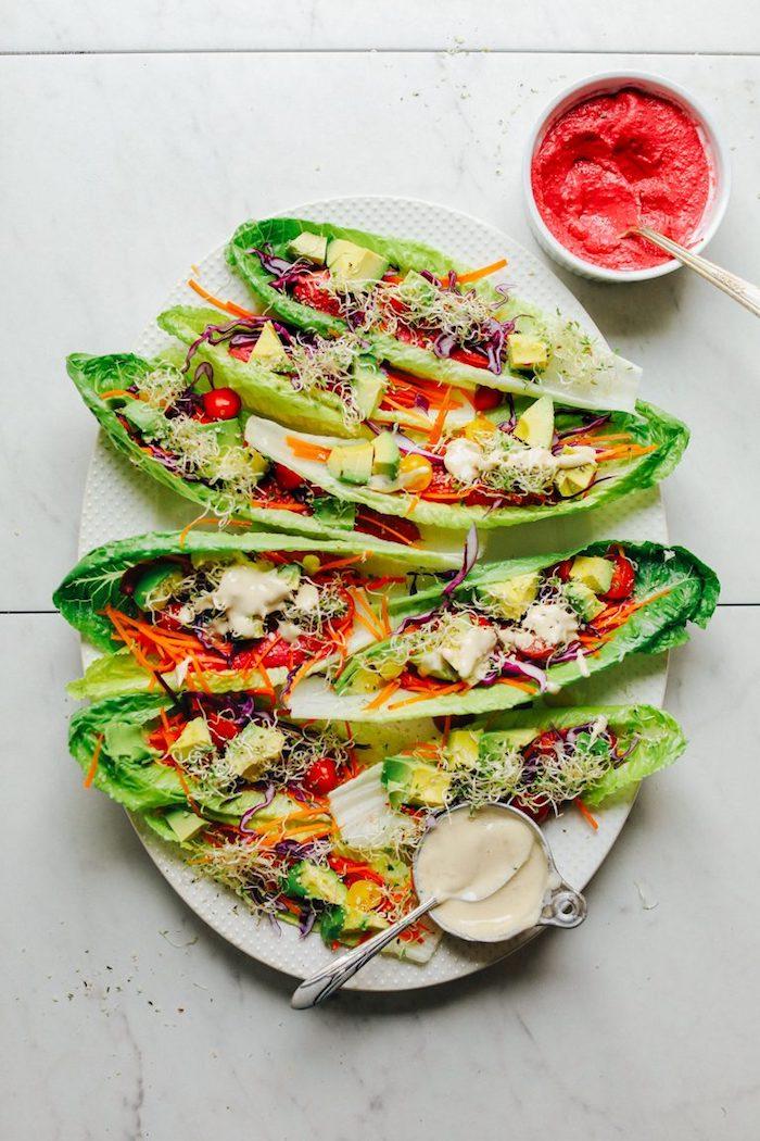 recette végétarienne de tacos en feuilles de laitue garnis d'avocat, de tomates cerises, de germes de luzerne et de sauce hoummous