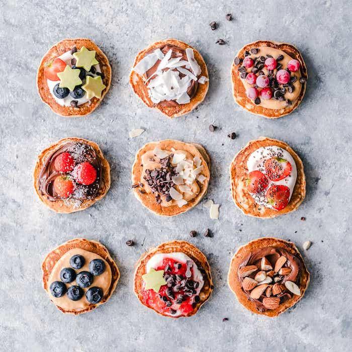 plusieurs idees de topping pancakes moelleuses avec chocolat, yaourt grec, beurre de noix, pépites de chocolat, fruits