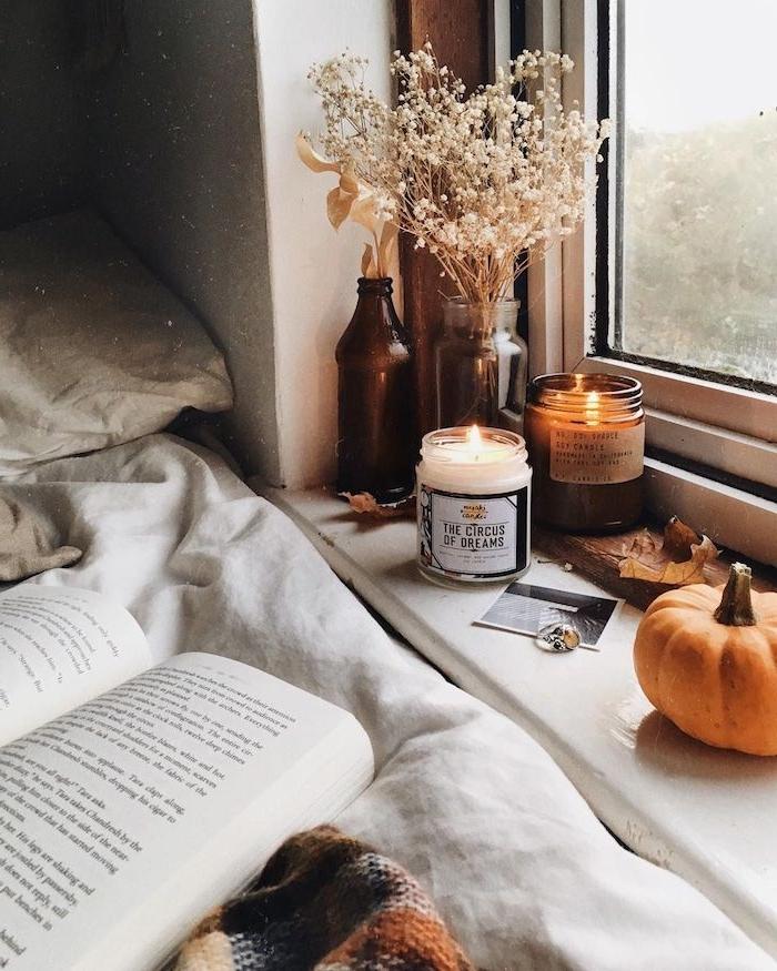 image fond ecran automne, deco rebord de fenetre en potiron, bougies decoratives, fleurs séchées, livre sur linge maison blanc