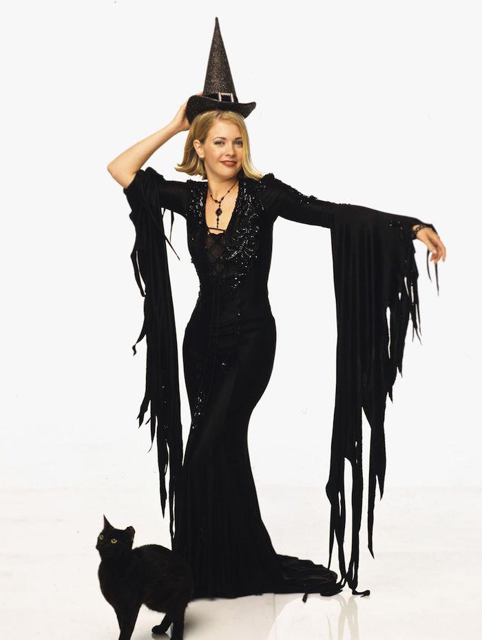 Sabrina the teenage witch déguisée comme sorcière robe noire longue et chat noir, style année 90, tenue etre une celebrite pour halloween