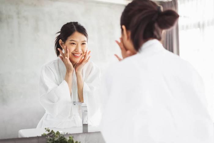 Femme dans la salle de bains, idée comment prendre soin de soi, femme souriante en robe de bain blanche