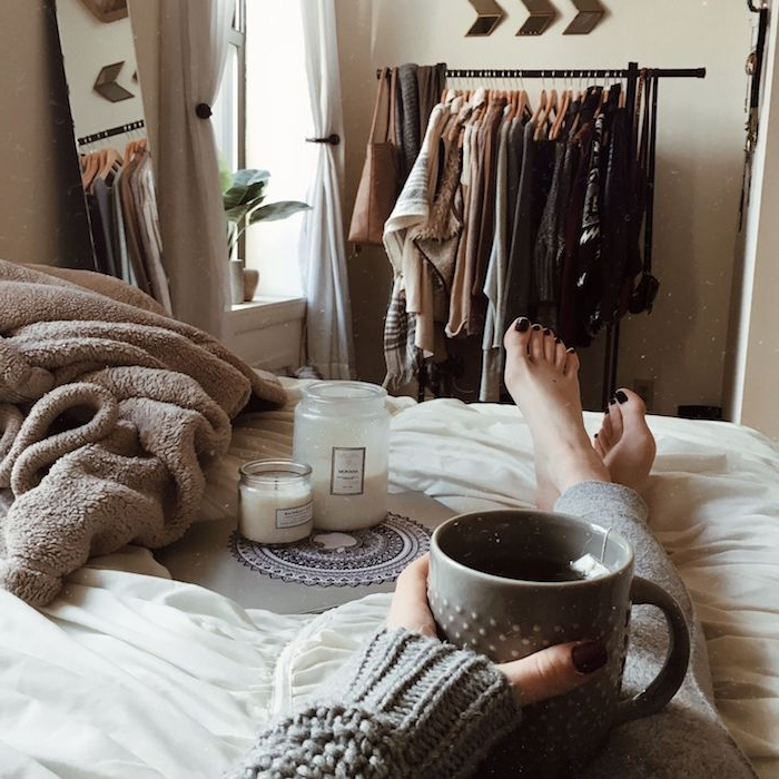 dressing chambre ouvert sur fond de mur beige, couverture de lit grise, linge d elit blanc, bougies aromatiques decoratives, ambiance hygge