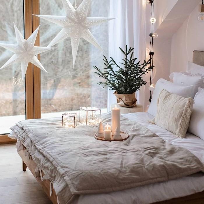 etoiles decoratives supendues, linge de lit gris et blanc, murs blanc, guirlande lumineuse interieur, deco guirlandes dans cubes de verre, deco chevet en mini sapin