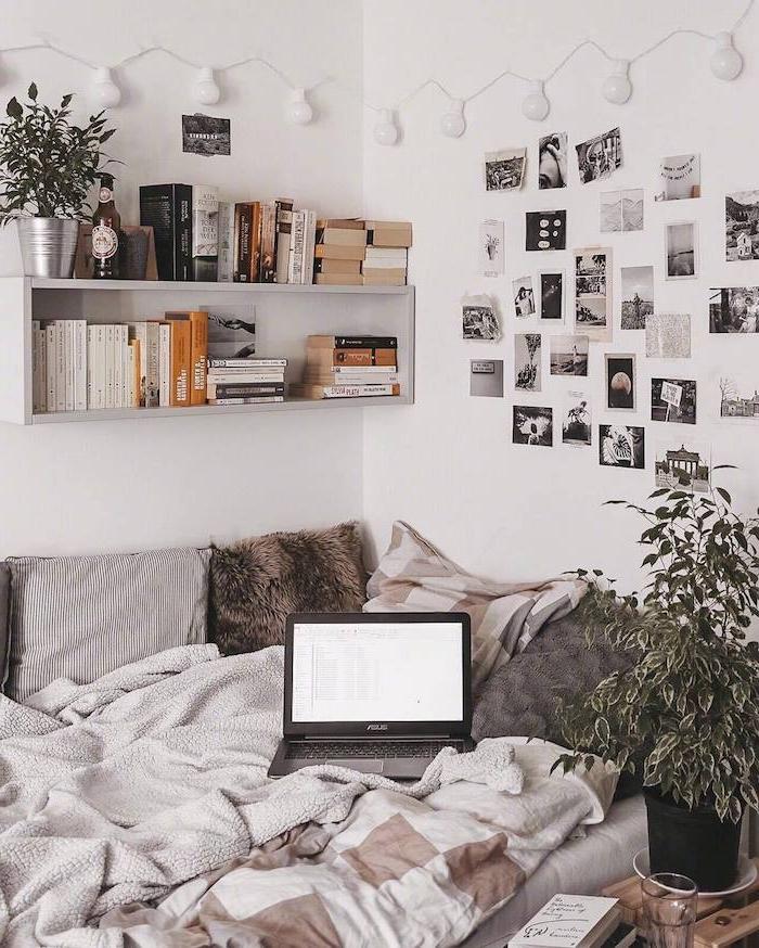 lit d angle avec coussins et parures de lit marron et gris, étagère murale blanche avec livres et plante, murs de photos noir et blanc, guirlande lumineuse guirlande