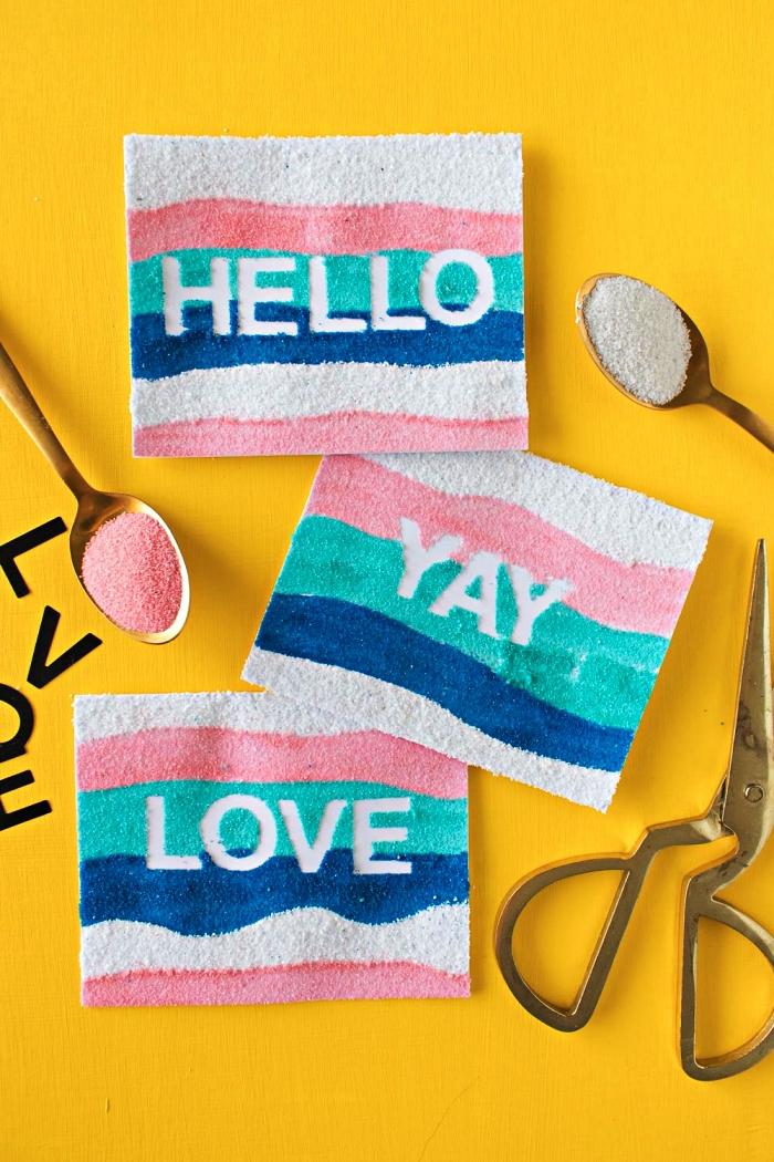 décoration d'une carte personnalisée à message avec des couches de sable coloré collé sur le papier, idée de bricolage facile avec du sable coloré