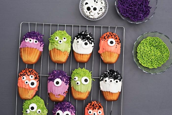 madeleines petits monstres d'halloween au glaçage coloré décorés de bonbons yeux en sucre, dessert facile pour le repas halloween