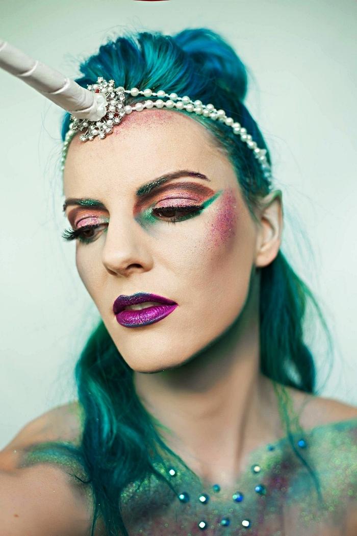 maquillage d'halloween artistique en rose, vert et violet pour un look licorne original, bijou de cheveux licorne avec perles sur cheveux bleu turquoise