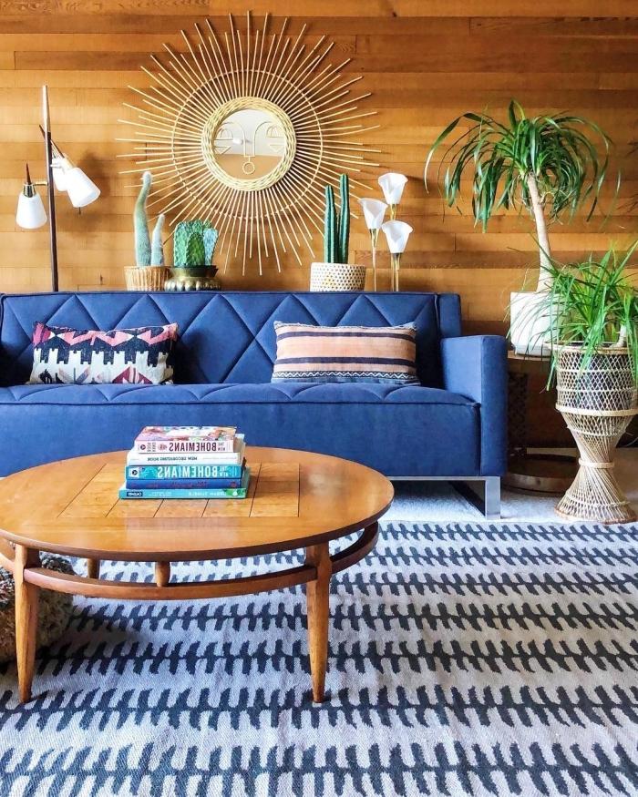 idée décoration de salon style jungalow aux murs en bois avec canapé velours en bleu marine et miroir rotin Justina Blakeney