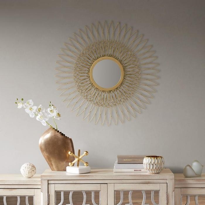 décoration salon luxueux aux murs neutres avec meubles bois et objets à finition or, modèle de miroir soleil doré