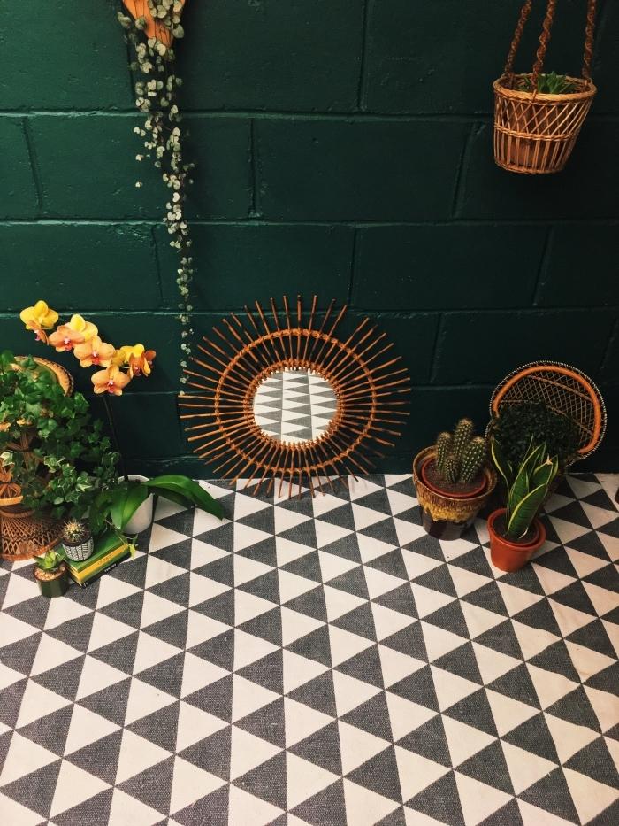 design intérieur tendance jungalow, déco pièce aux murs en briques peintes vertes avec tapis imitation carreaux, modèle miroir osier