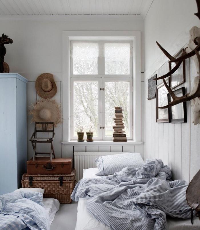 mur lambris blanc, rangement malles recuclées, linge de lit noir et blanc, armoire blanc cassé, deco chambre vintage rustique