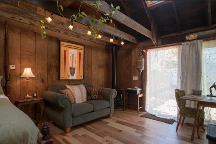 aménagement grange de style rustique, décoration chambre à coucher à design chalet bois foncé avec canapé tissu