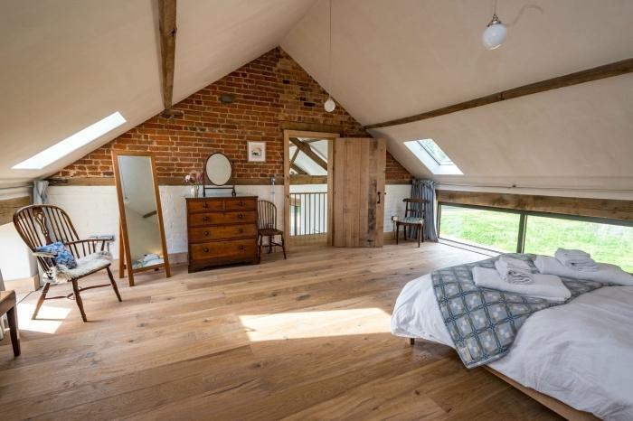 comble aménageable dans une grange maison, décoration pièce blanc et bois avec mur en briques et accents métal