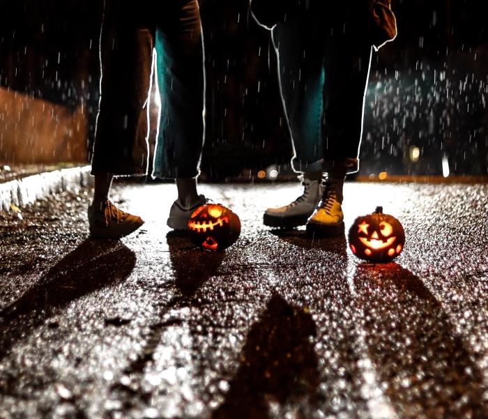 image halloween pour écran iphone, photo de teens habillés en jeans sous la pluie avec petites citrouilles sculptées