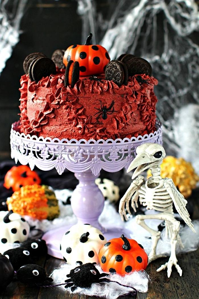 gateau d'halloween au glaçage crème beurre rouge, décoré de biscuits oreo et d'une citrouille décorative