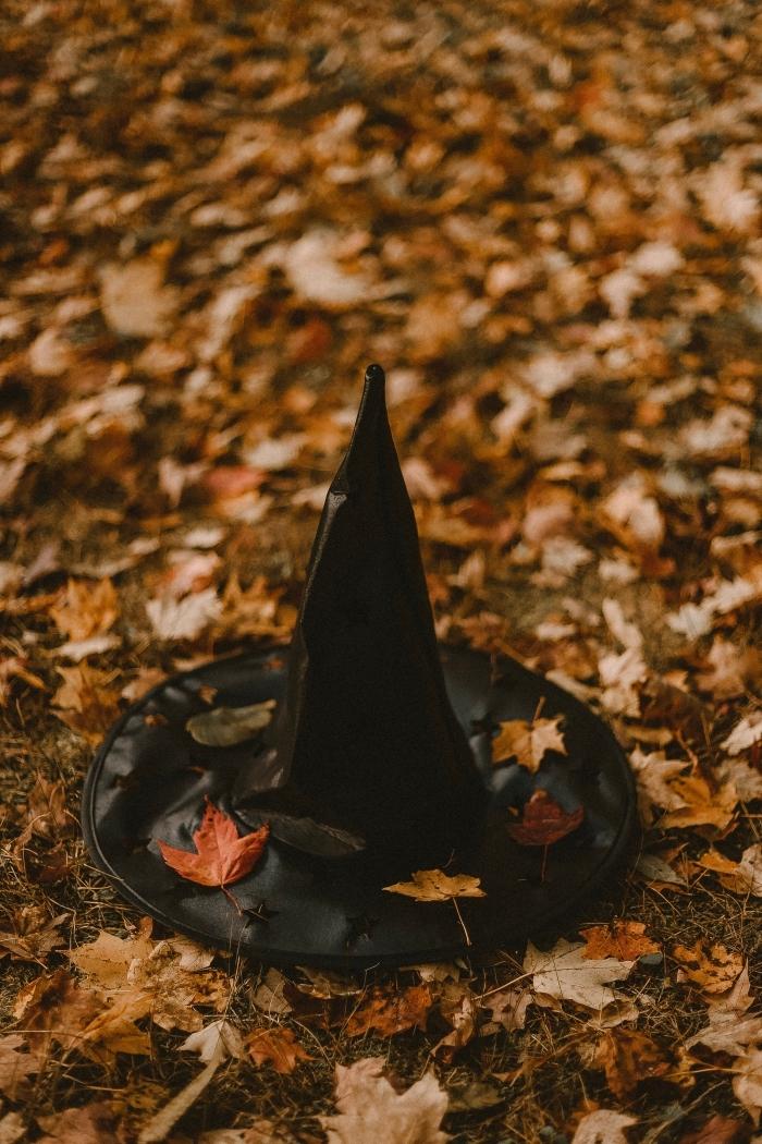 wallpaper sorcière halloween pour iphone, photo de chapeau sorcière sur feuilles séchées colorés d'automne