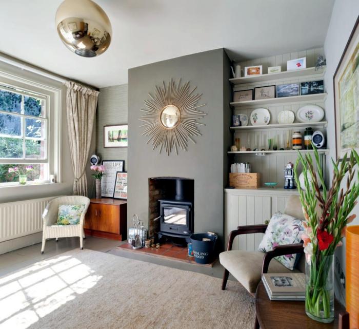 décoration petite salle de séjour avec cheminée, modèle de miroir soleil doré accroché sur un mur en gris clair
