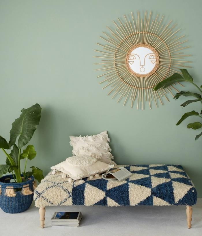 déco murale avec miroir soleil rotin de Justina Blakeney, idée nid lecture cocooning avec banquette bois et accessoires en beige et bleu marine