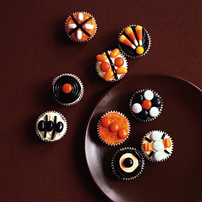 cupcakes d'halloween au glaçage orange, noir et blanc, décorés de confieseries, idée de petit gateau halloween