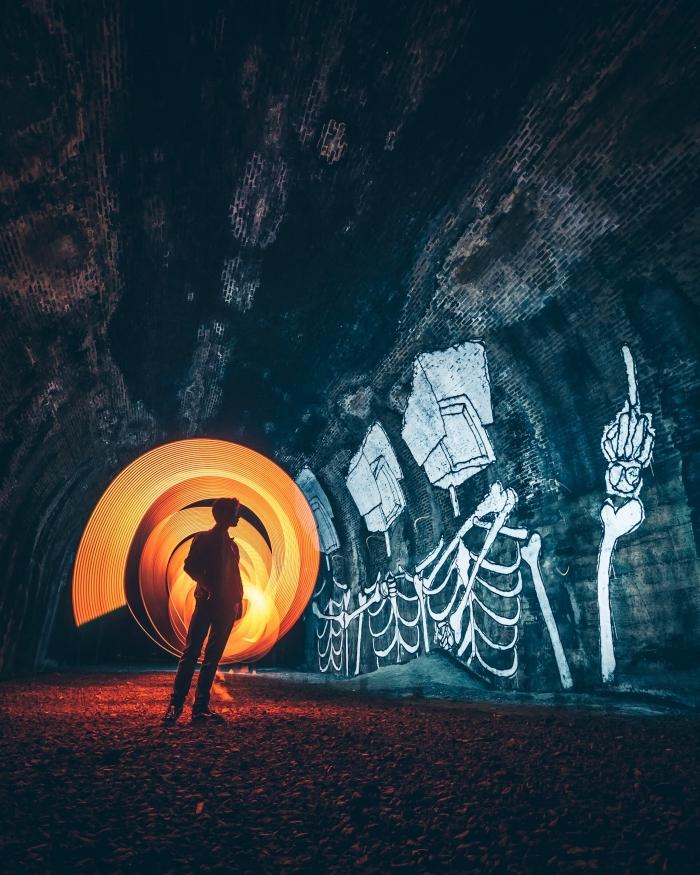 photographie abstraite, photo de garçon dans une grotte avec dessins à motifs squelettes, idée wallpaper portable pour Halloween