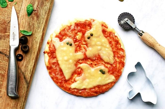 recettes apéritives sur le thème d'halloween, pizza halloween hantée au fromage et sauce tomate