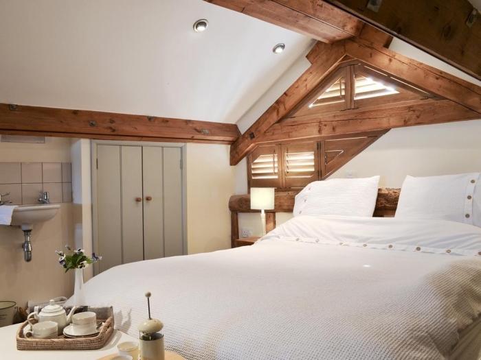 idée aménagement de combles, modèle de chambre à coucher rustique aux murs blancs avec accents en bois