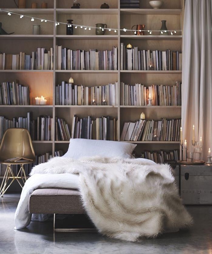 sol effet beton, lit recouvert de peau de mouton couverture originale, lit gris, bibliothèque originale surchargée de livres