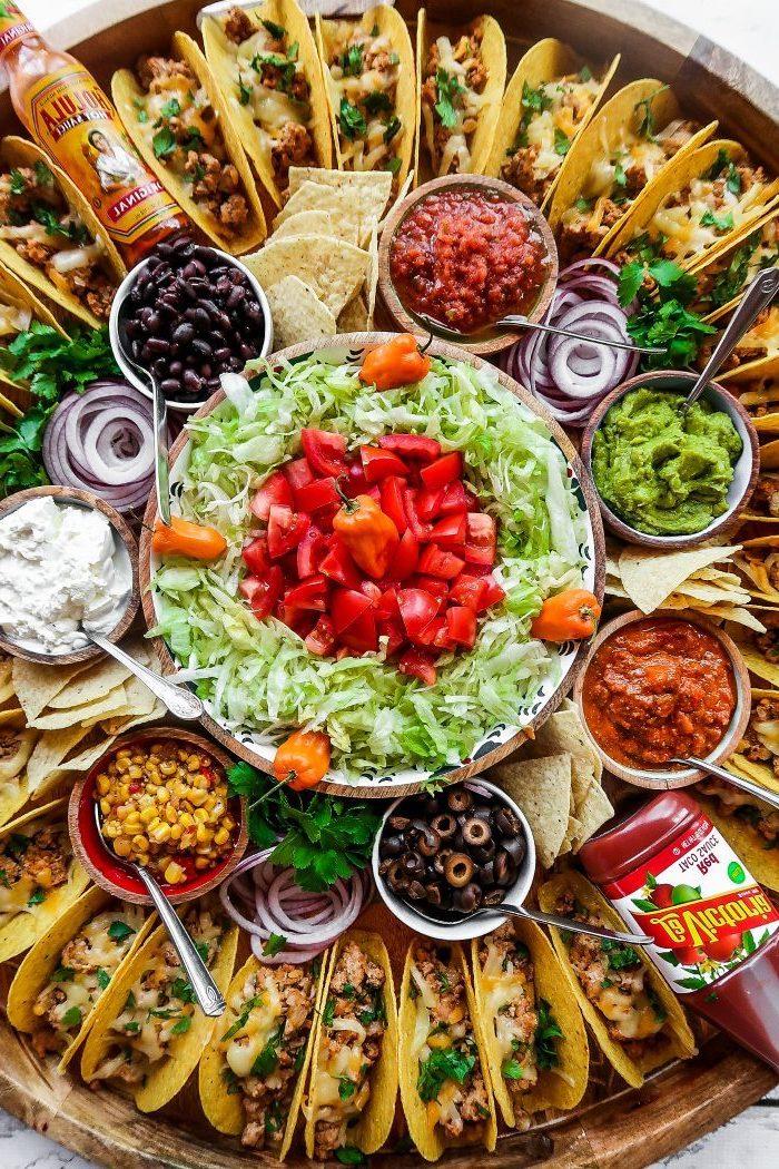 idée d'apéro dinatoire facile pour 10 personnes, plateau avec mini-tacos accompagnés de sauces et garnitures diverses