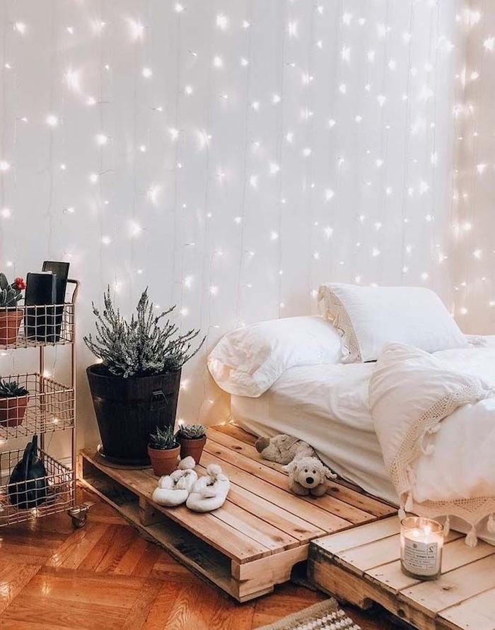 pluie de lumières, plusieurs guirlandes lumineuses pour decorer un mur de fond blanc, lit en palette de bois, avec matelas et linge blanc, etagere rangement plantes à roulettes