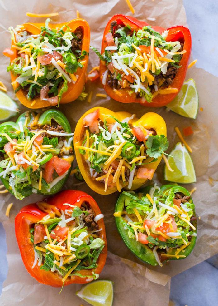 des poivrons crus farcis de tomates, cheddar râpé et de salade verte façon tacos végétariens